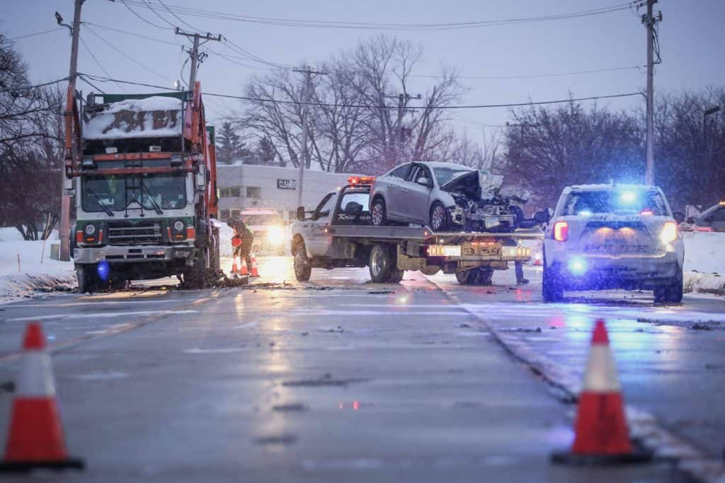 Woman in life-threatening condition after fiery crash involving garbage truck, sedan in Woodstock